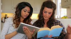 Women learning with book and tablet pc Stock Footage
