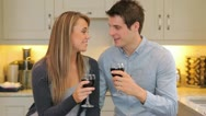 Couple sitting in the kitchen drinking wine Stock Footage