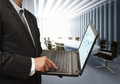business man using laptop computer in board room - stock photo