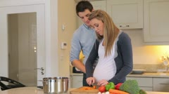 Pregnant wife cutting vegeatables and eating them with husband Stock Footage