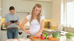 Woman chopping vegetables then feeding husband jokingly Stock Footage