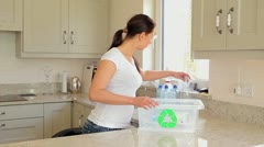 Woman putting bottles into recycling bin Stock Footage