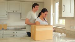 Woman packing moving box with man carrying boxes - stock footage