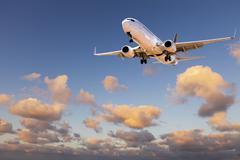 Aircraft  landing from sunset sky Stock Photos