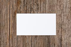 empty white card over old textured wooden background - stock photo