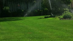 Lawn sprinkler cris-cross each other in back yard - stock footage