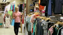 Woman looking at clothes on rail Stock Footage