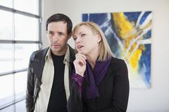 Couple looking at art in art gallery Stock Photos