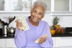 African American woman counting money in kitchen - stock photo
