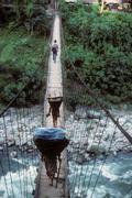porters carrying loads across suspension bridge - stock photo
