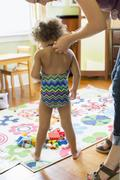 Mother putting bathing suit on daughter Stock Photos