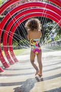 Mixed race girl playing in fountain Stock Photos