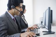 Mixed race business people using computers Stock Photos