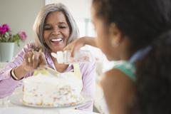 African American grandmother and granddaughter decorating a cake Stock Photos