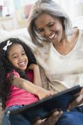 African American grandmother and granddaughter looking at digital tablet - stock photo