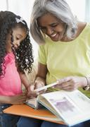 African American grandmother and granddaughter reading a book Stock Photos