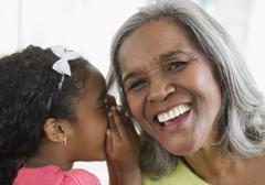 African American girl telling secret to grandmother - stock photo