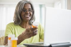 African American woman holding pill bottle and using laptop Stock Photos