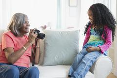African American woman taking pictures of granddaughter - stock photo