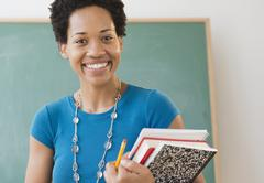 African American woman carrying school books - stock photo