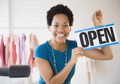 African American woman holding up open sign - stock photo