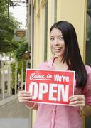 Asian woman holding open sign Stock Photos