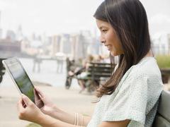 Asian woman using digital tablet outdoors Stock Photos