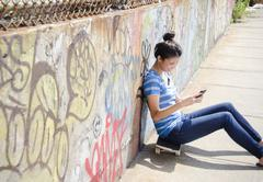 Asian woman sitting on skateboard using cell phone - stock photo