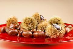 Sweet chestnuts on a red plate Stock Photos