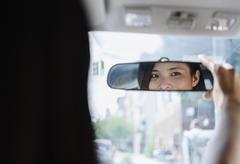Asian woman adjusting rear-view mirror - stock photo