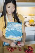 Asian woman cutting strawberries Stock Photos