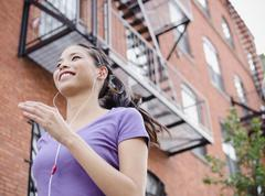 Asian woman jogging and listening to music - stock photo