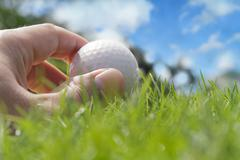 golfer putting a ball on the green - stock photo