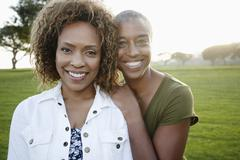 African American mother and daughter standing in park - stock photo