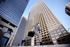 Businessman running past highrise building Stock Photos