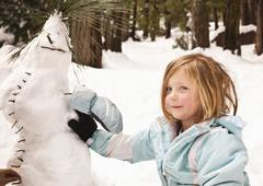 Caucasian girl making strange snowman Stock Photos