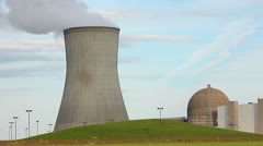 Nuclear power plant - cooling tower with steam and reactor building - stock footage