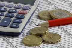 Pencil,calculator & coins on a spreadsheet Stock Photos