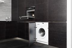 Build-in washing machine and cooker on modern black kitchen Stock Photos