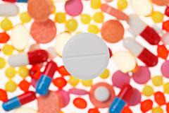 one big tablet (pill) macro view on blurred multicolored drugs background, me - stock photo