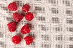 many red ripe raspberry fruit, on gray linen table cloth with copy space desi - stock photo