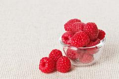 still life with red raspberry and glass bowl on gray linen table cloth, copy  - stock photo