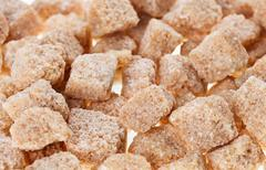 many brown lump cane sugar cubes , food background - stock photo