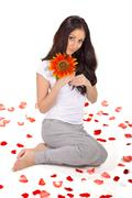 young beautiful lady holding sunflower near face - stock photo