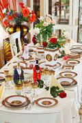 Luxuriant table appointments with red  china porcelain and rose flowers Stock Photos