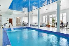 Indoor big blue swimming pool interior in modern minimalism style Stock Photos