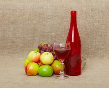 Still-life - bottle and fruit against a canvas Stock Photos