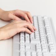 Female hands work on computer keyboard Stock Photos