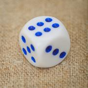 Plastic dice with blue dots on canvas close up Stock Photos