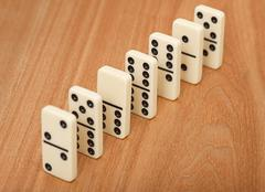 Line from seven dominoes on wooden surface Stock Photos